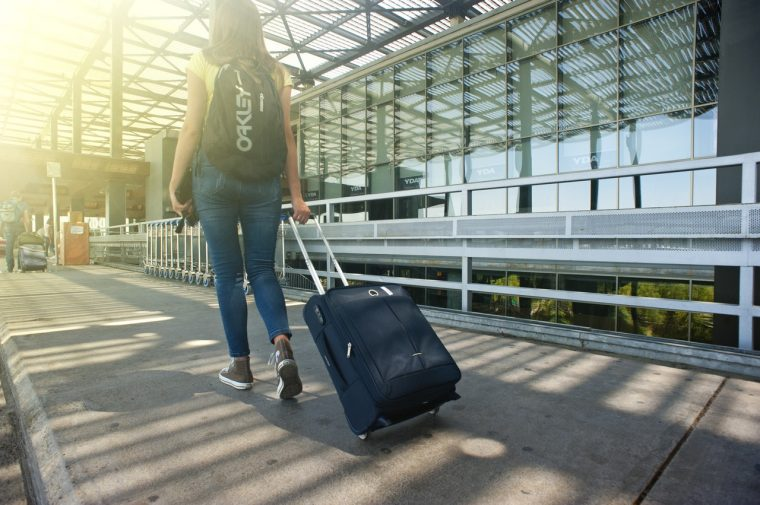 dziewczyna z walizką na lotnisku - podroz samolotem