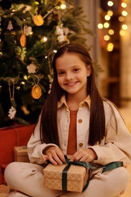 Mikołajki - zwyczaje. Uśmiechnięta dziewczynka z prezentem