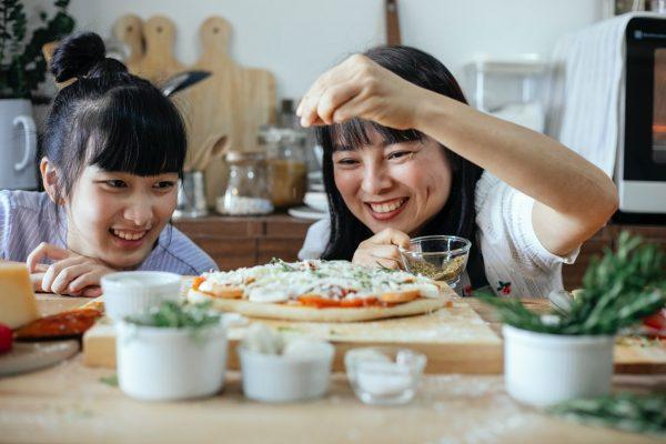 Jak zrobić pizzę? - dwie kobiety w kuchni przygotowujące pizzę
